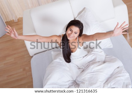 Pretty young woman snuggling down in bed as she smiles up at the camera