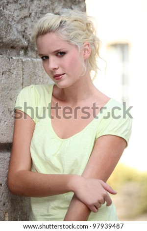 Pretty young woman standing next to a stone wall - stock photo