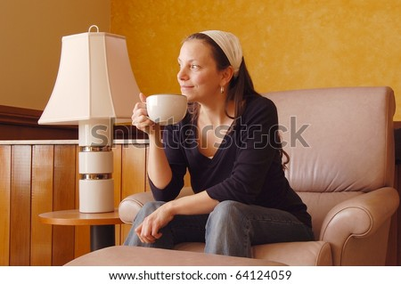 Pretty Young Woman Staring Dreamily on a Recliner while Sipping Coffee