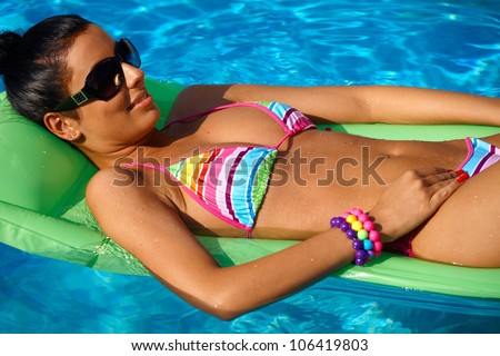 Pretty young woman sunbathing in swimming pool, laying on airbed.