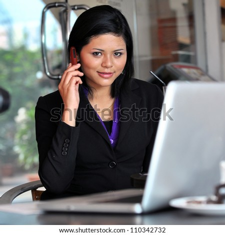Pretty young woman surfing internet on laptop and make phone call