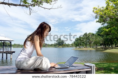 Pretty young woman surfing internet on laptop outdoors.