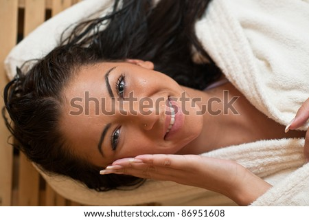 Pretty Young woman take a steam bath treatment at finish wooden sauna while wearing white towel