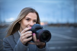 Pretty, young woman taking photos with her professional dslr camera