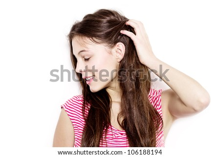 pretty young woman touching her hair and looking sideways - isolated against white background