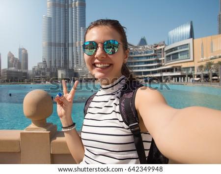 Pretty young woman tourist takes selfie portrait at Dubai fountain,Burj Khalifa. Beautiful female student takes photo for travel blog.