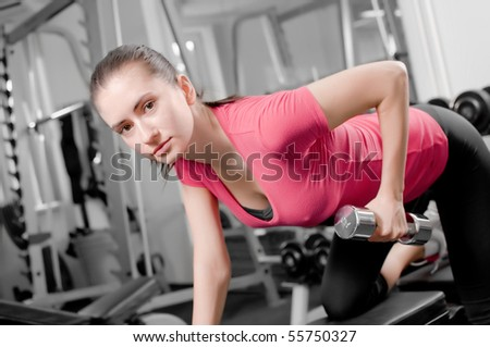 pretty young woman training with dumbbells in a gym