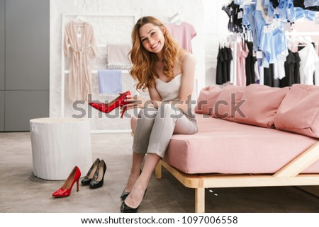 Pretty young woman trying on new shoes at the clothing store