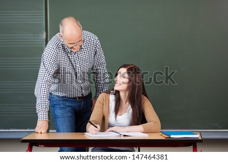 Pretty young woman university student with a middle-aged male lecturer or tutor leaning over her at her desk to help her with her project against a green blackboard