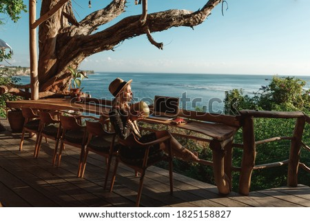 Pretty young woman using laptop in cafe with sea view. Freelancer working remotely from beach cafe, drink coconut and use laptop