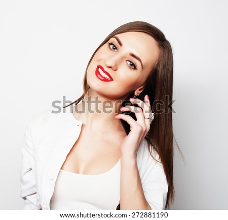 Pretty young woman using mobile phone over white background #272881190