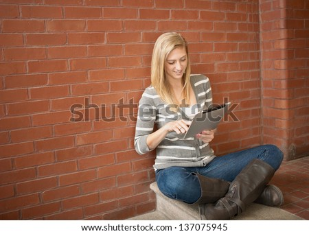 Pretty young woman using tablet computer studying