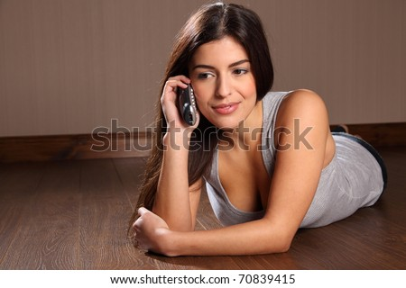 Pretty young woman using telephone at home - stock photo