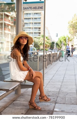 Pretty young woman waiting for a bus in the French Riviera in Nice, France.
