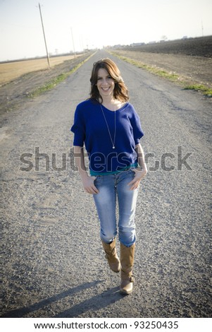 Pretty Young Woman Walking Down The Middle Of Road In Country