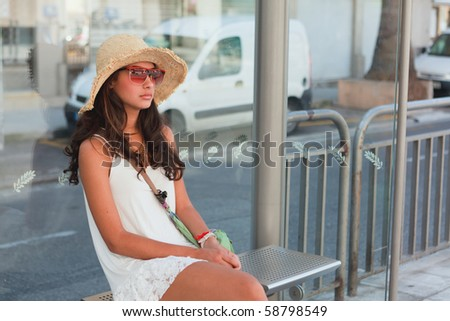 Pretty young woman wearing a hat waiting for a bus to arrive in Nice, France.