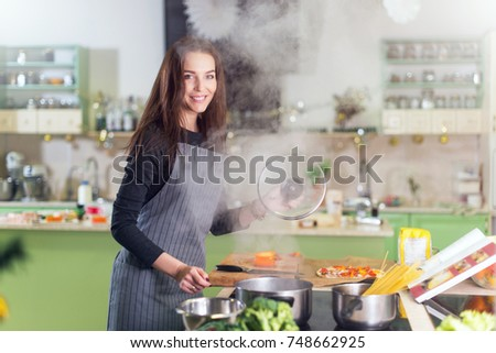 Pretty young woman wearing apron making dinner cooking spaghetti following the recipe in a book standing in kitchen