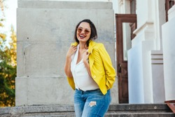 Pretty young woman wearing bright colorful jacket walking on the city street. Casual fashion, plus size model.