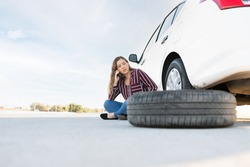 Pretty young woman with a flat tire sitting on the road next to her car. Woman calling for a tow truck and road assistance help