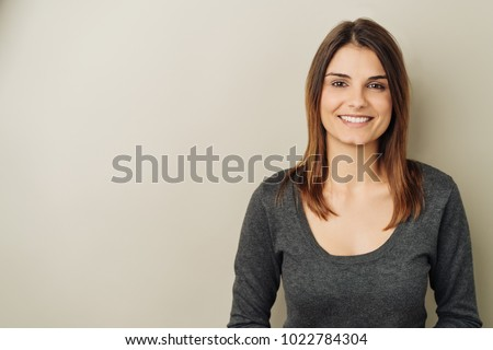 Pretty young woman with a happy beaming smile and shoulder length brown hair against a neutral studio background with copy space