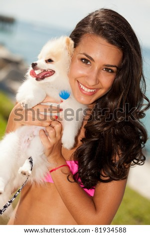 Pretty young woman with a pomeranian puppy at the beach.
