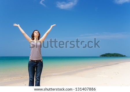Pretty young woman with arms raised and eyes shut standing on the tropical beach relaxed. Expressing positivity
