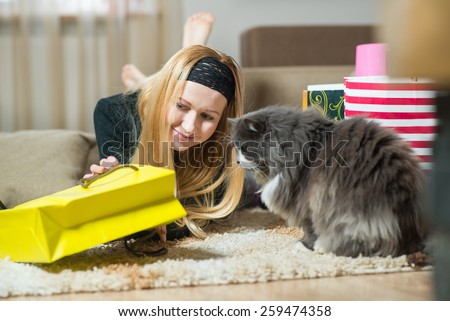 Pretty young woman with cat looking into the bag from store at home. Woman came home from the shopping