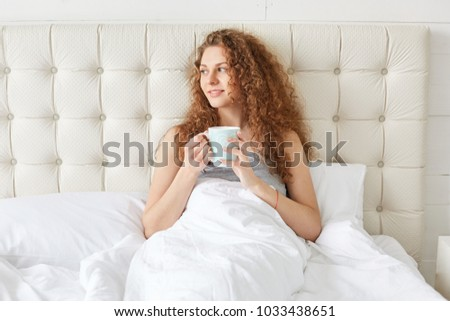 Stock Photo Pretty young woman with curly hair has morning aromatic coffee in bed, looks pleasantly away, enjoys sunrise, has good relax in bedroom. Relaxed adorable female drinks hot tea in bed alone.