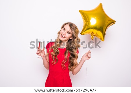 a92d9bc58eaa Pretty young woman with gold star shaped balloon smiling and drinking  champagne over white background #