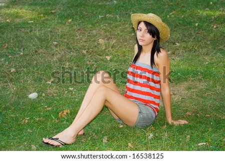 Pretty young woman with hat sitting on a grass field