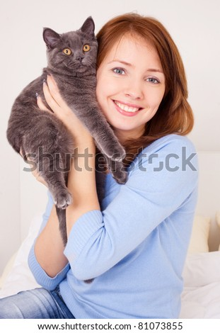 pretty young woman with her cat on the bed at home - stock photo