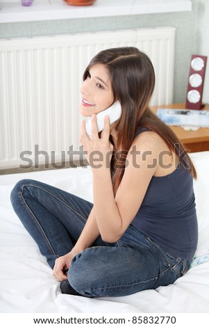 Pretty young woman with phone sitting on bed at home