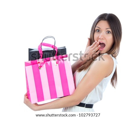Pretty young woman with shopping bags after successful shopping, smiling and looking at the camera on a white background