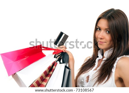 Pretty young woman with shopping bags, credit gift card in one hand buying presents, smiling and looking at the camera isolated on a white background