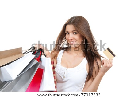 Pretty young woman with shopping bags, credit gift card in one hand buying presentsin supermarket, smiling and looking at the camera isolated on a white background