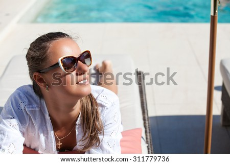 Pretty young woman with sun glasses relaxing at the luxury poolside. Girl at travel spa resort pool. Summer luxury vacation.