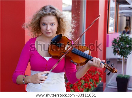 Pretty young woman with violin in the street