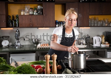 Pretty young woman working in a big kitchen
