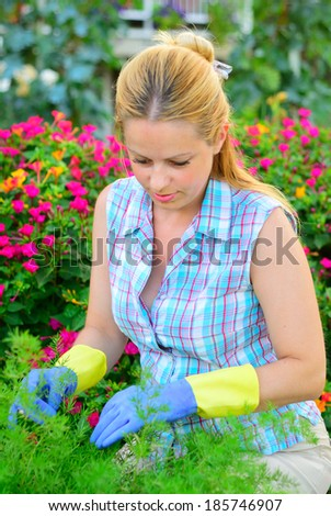 Pretty young woman working in a flower garden, natural model, natural lighting