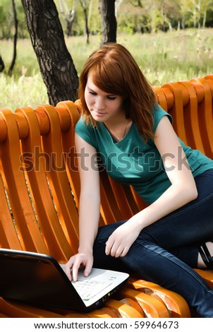 pretty young woman working with laptop in city park