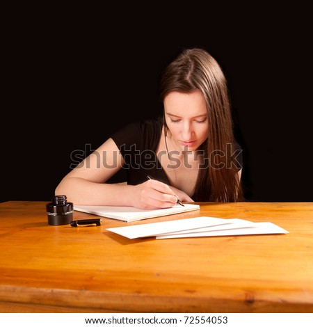 Pretty young woman writing a letter at an old table
