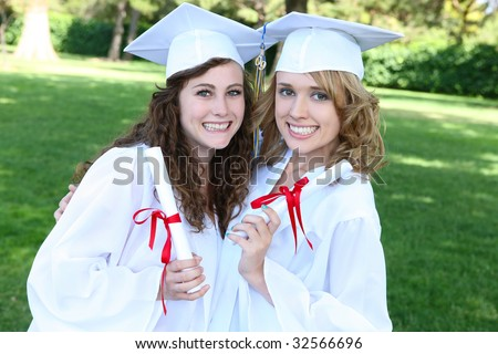 Pretty young women at graduation hugging with diplomas