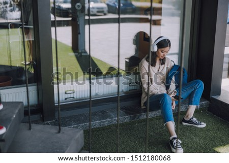 Pretty young young woman using her new cellphone. Modern technology concept