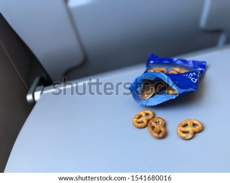 pretzels on a plane, snacks and food on a plane, pretzel snacks on a plane for traveling, travel snacks, airplane tray with snacks and pretzels on it, folding tray on a plane.