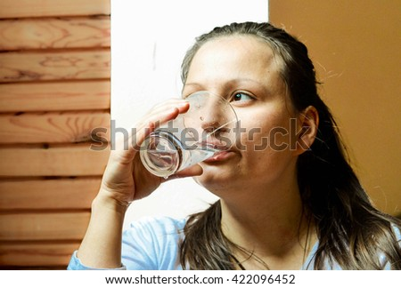 Preventing of dehydration -  portrait of pretty young woman drinking the glass of water
