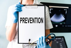 Prevention is better than cure - Female doctor's hand holding medical clipboard and stethoscope. Concept of Healthcare And Medicine. Ultrasound medical device for diagnostics for background.