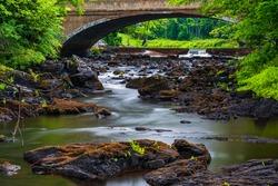 Price Rapids Tweed Ontario Canada on overcast rainy summer day, beautiful jagged metamorphic rocks, bridge and rapids