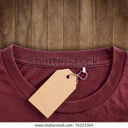 price tag hang over brown t-shirt on wood background