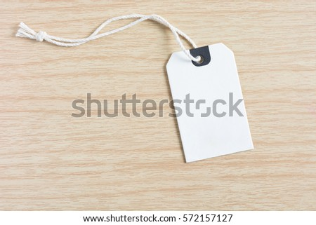 Price tag or label. White paper price tag is empty with burlap rope on wooden table background. #572157127