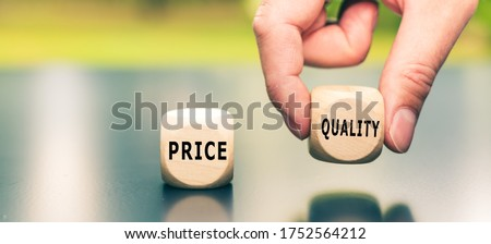 "Price versus Quality. The cube with the word ""quality"" is selected by a hand."